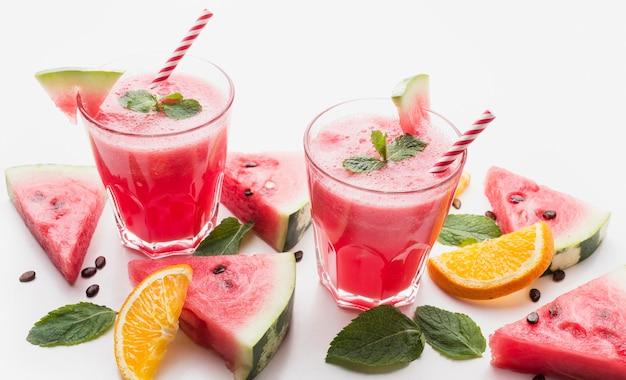 Angle élevé de deux verres à cocktail pastèque avec menthe et pailles