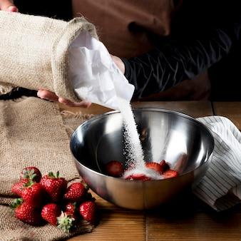 Angle élevé du chef ajoutant du sucre dans un bol de fraises