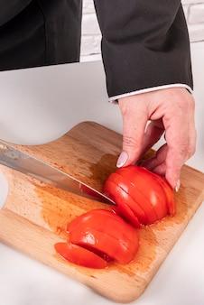 Angle élevé du chef féminin, couper les tomates