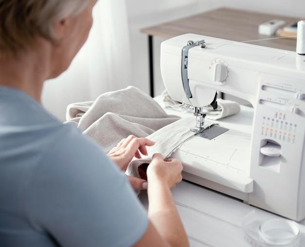 Angle élevé du tailleur féminin à l'aide de la machine à coudre