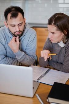 Angle élevé du tuteur donnant des leçons à l'étudiant à la maison