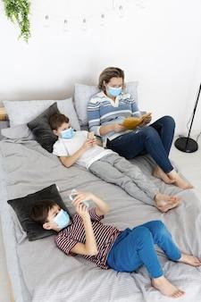 Angle élevé des enfants au lit avec des masques médicaux et mère lisant un livre