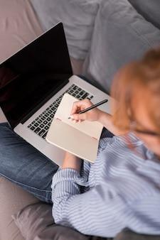 Angle élevé de l'enseignante sur le canapé tenant une classe en ligne