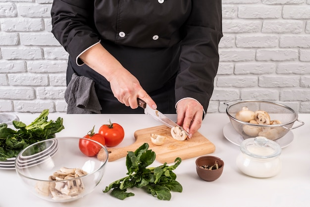 Angle élevé de femme chef coupant les champignons et les tomates