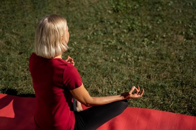 Angle élevé de femme à l'extérieur, faire du yoga