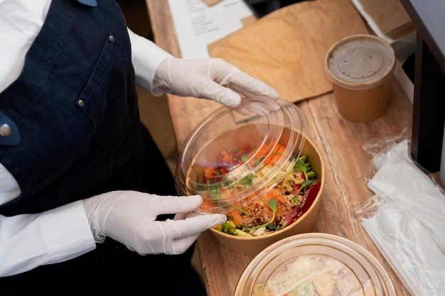 Angle élevé de femme avec des gants d'emballage de salade à emporter