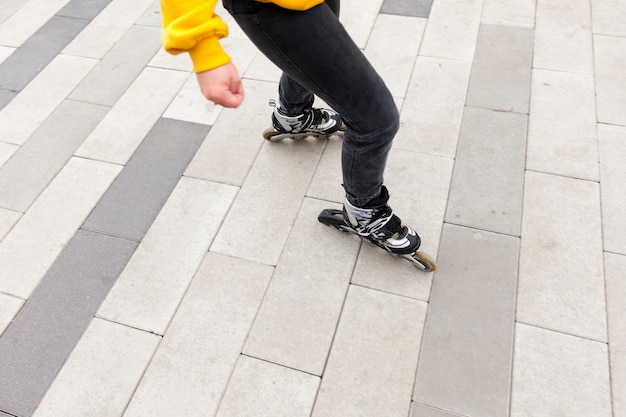 Angle élevé de femme avec des patins à roues alignées sur la chaussée