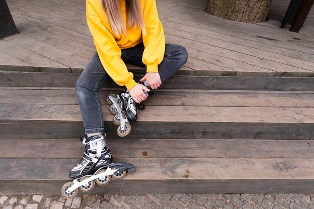 Angle élevé de femme avec patins à roues alignées et pull