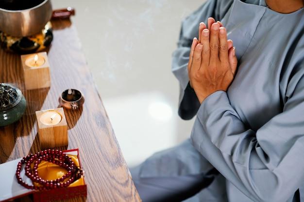 Angle élevé de femme priant devant des bougies