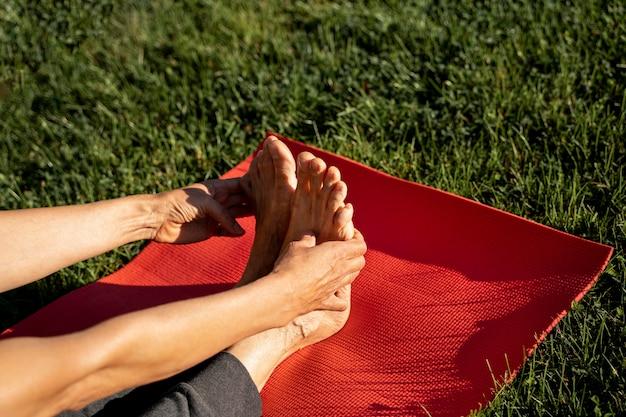Angle élevé de femme qui s'étend à l'extérieur pour le yoga