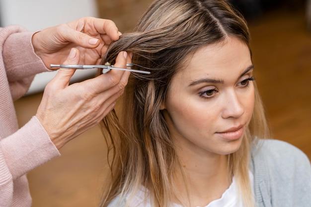Angle élevé de femme se faire couper les cheveux