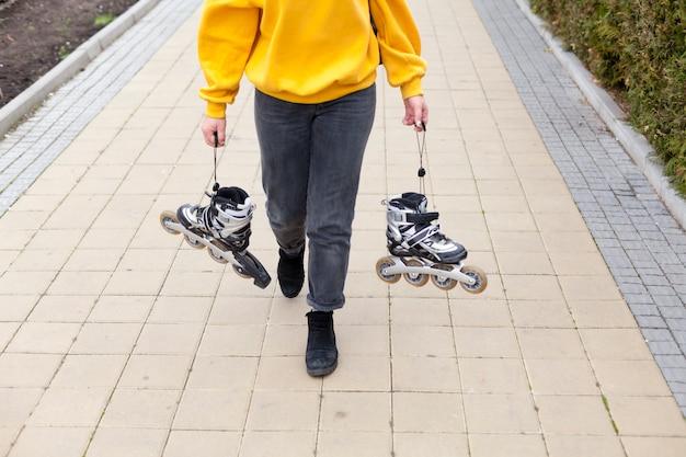 Angle élevé sur femme tenant des patins à roues alignées en marchant