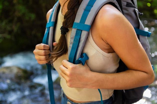 Angle élevé de femme tenant son sac à dos tout en explorant la nature