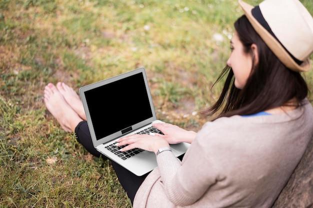 Angle élevé de femme travaillant sur un ordinateur portable à l'extérieur