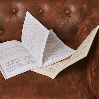 Angle élevé de feuilles de musique sur le canapé