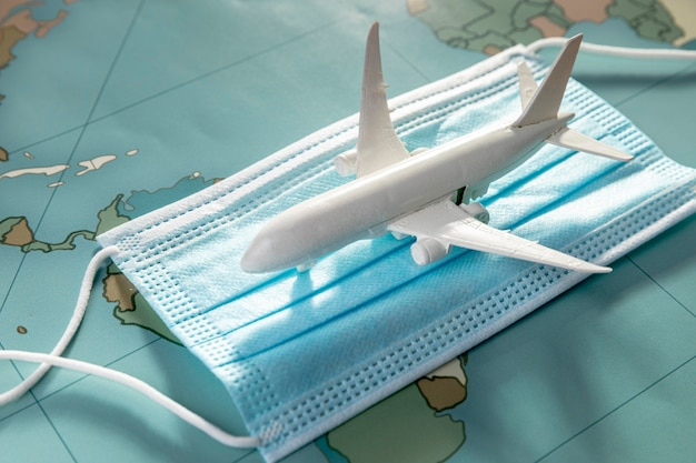Angle élevé de figurine d'avion sur masque médical