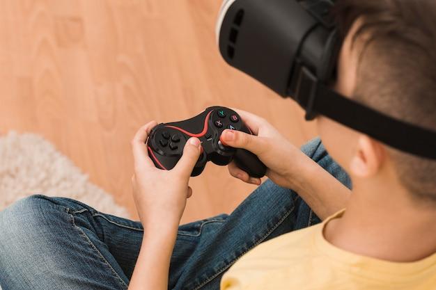 Angle élevé de garçon jouant à des jeux vidéo avec un casque de réalité virtuelle