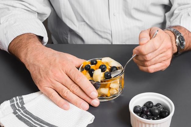 Angle élevé d'homme mangeant des myrtilles dans un bol