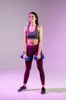 Angle élevé jeune femme exerçant avec des poids