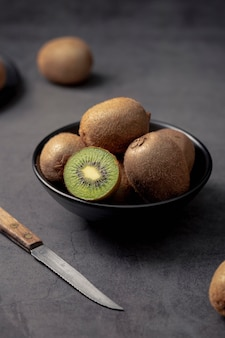 Angle élevé de kiwi dans un bol avec couteau