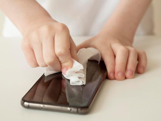 Angle élevé des mains désinfectant le smartphone