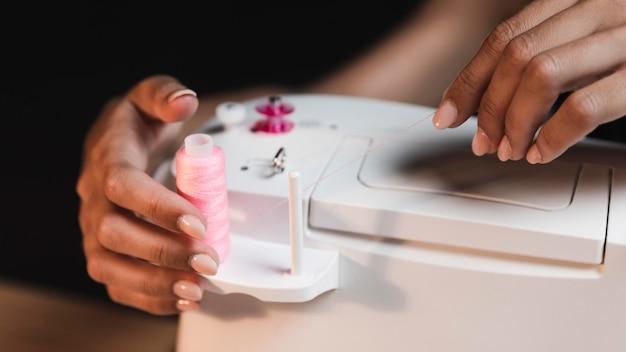 Angle élevé des mains féminines manipulant la machine à coudre