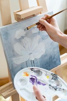 Angle élevé de mains féminines peignant une fleur à la maison