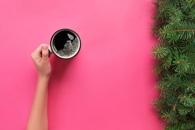 Angle élevé des mains de femme tenant une tasse de café rose