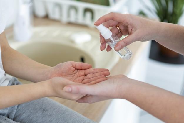 Angle élevé de la mère désinfectant les mains de l'enfant