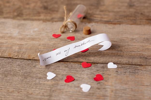 Angle élevé de message pour la saint-valentin avec tube et coeurs