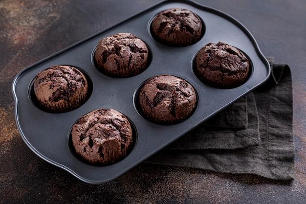 Angle élevé de muffins au chocolat dans un plateau avec un chiffon