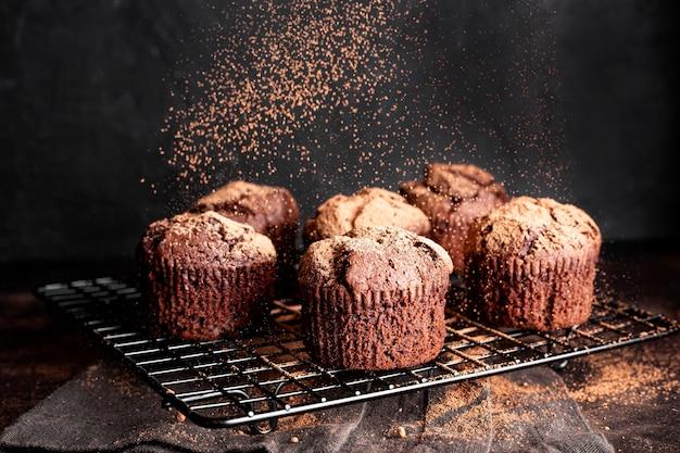 Angle élevé de muffins au chocolat sur une grille de refroidissement en poudre avec du cacao