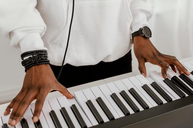 Angle élevé de musicien masculin jouant du clavier électrique