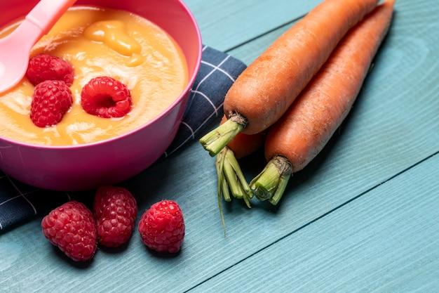Angle élevé de nourriture pour bébé avec des framboises et des carottes