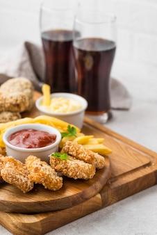 Angle élevé de nuggets de poulet frit avec sauce et boissons gazeuses
