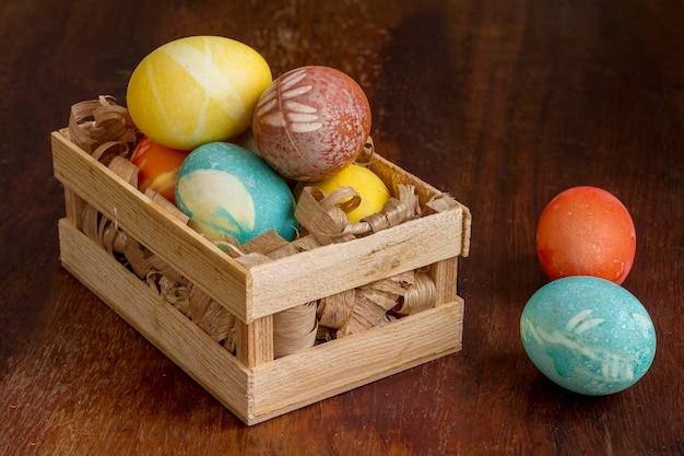 Angle élevé d'oeufs colorés pour pâques dans une caisse en bois
