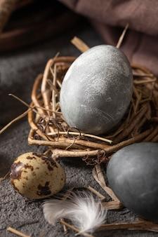 Angle élevé d'oeufs de pâques dans le nid fait de brindilles