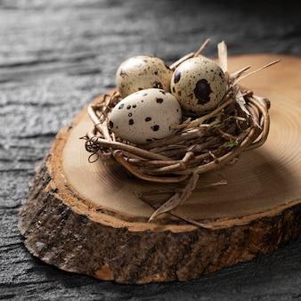 Angle élevé d'oeufs de pâques dans le nid d'oiseau sur le dessus de la planche en bois