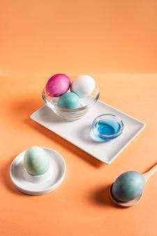 Angle élevé d'oeufs de pâques peints colorés sur plaque avec colorant et cuillère