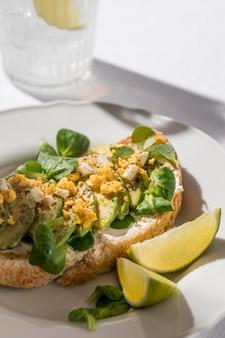 Angle élevé de pain grillé à l'avocat sur une assiette avec verre d'eau glacée et limes