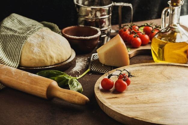 Angle élevé de pâte à pizza avec planche de bois et fromage parmesan