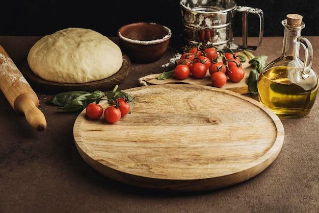 Angle élevé de pâte à pizza avec planche de bois et tomates