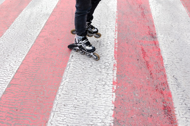 Angle élevé des patins à roues alignées sur le passage pour piétons