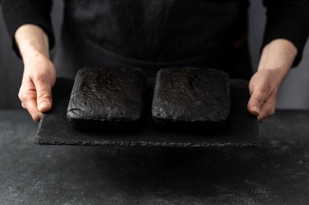 Angle élevé de pâtissier tenant des morceaux de gâteau
