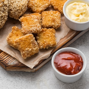 Angle élevé de pépites de poulet frit avec deux sauces différentes