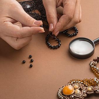 Angle élevé de personne faisant des travaux de perles