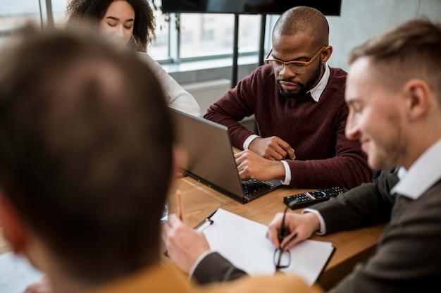 Angle élevé de personnes au bureau lors d'une réunion
