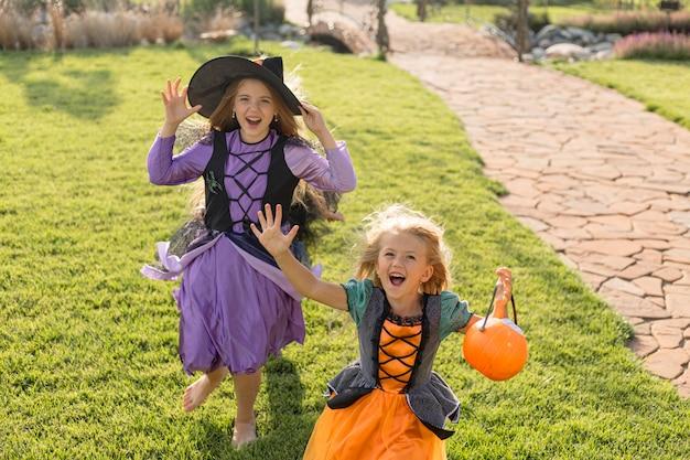 Angle élevé de petites filles mignonnes avec des costumes d'halloween