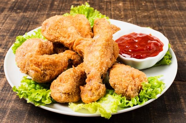 Angle élevé de pilons frits avec du ketchup