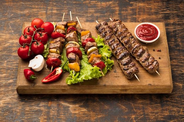 Angle élevé de planche à découper avec de délicieux kebab et légumes